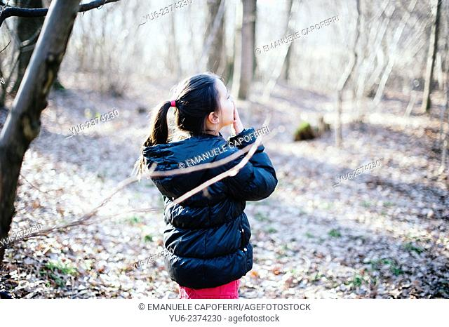 Little girl playing in the woods