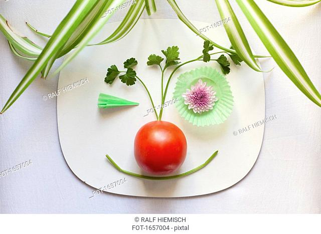 High angle view of funny face made from vegetables on plate at table