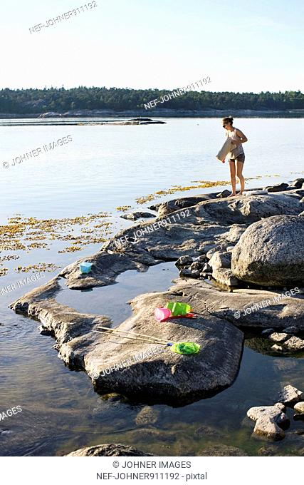 Woman on a rock by the sea, Sweden