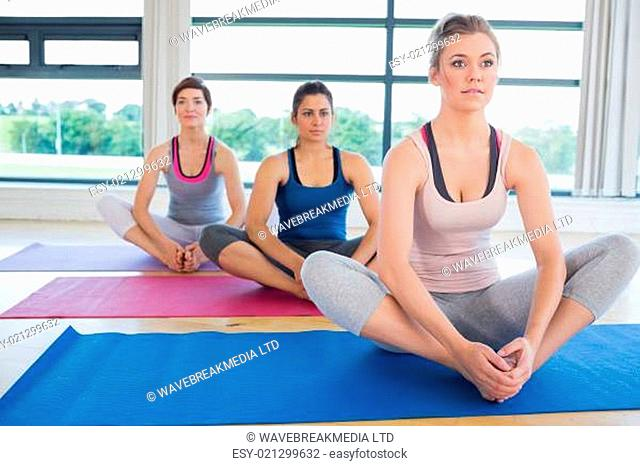 Women sitting in bound angle yoga pose in fitness studio