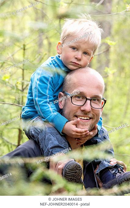 Father walking with son in forest