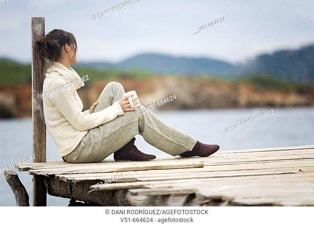 Young woman sitting on a bridge