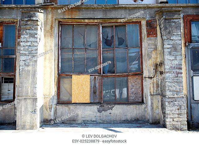 architecture and construction concept - old industrial building with broken glass window