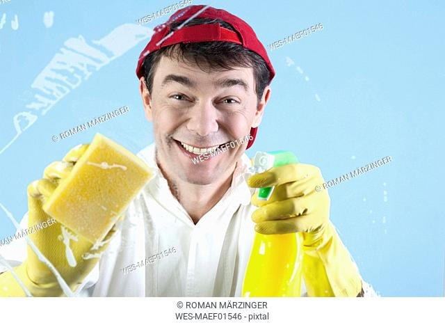 Man holding spray bottle, cleaning window, portrait