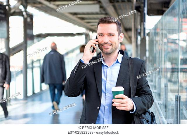 View of a Young attractive business man using smartphone while drinking coffee