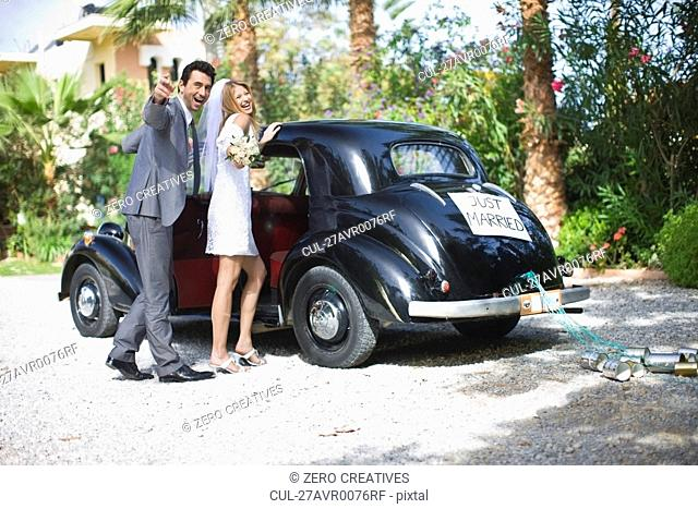 Bridal couple in front of car