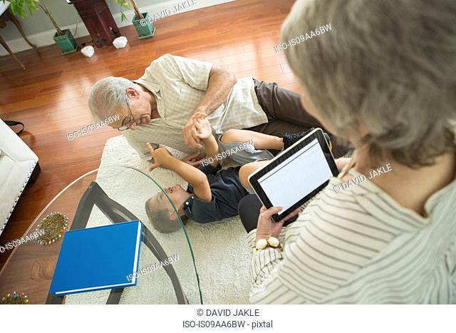 Senior man tickling grandson on rug