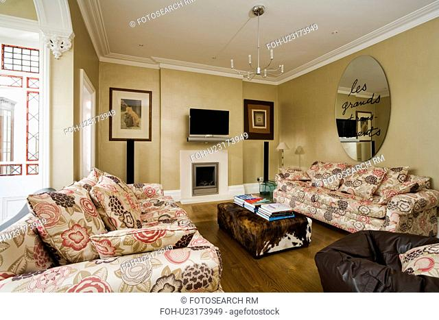 Circular modern mirror above patterned sofa in beige living room with faux animalskin coffee table