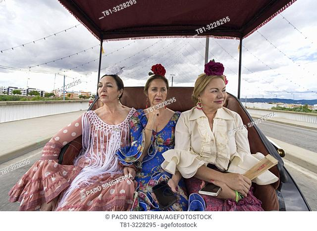 Three women in traditional andalusian costume in a car. Cordoba, Andalusia, Spain