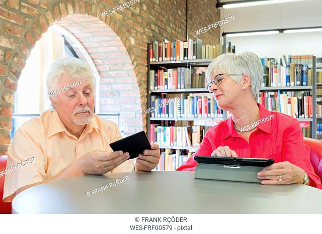 Senior couple with tablet and e-book in a city library