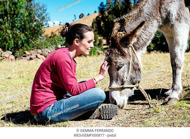 Peru, Amantani Island, woman stroking donkey
