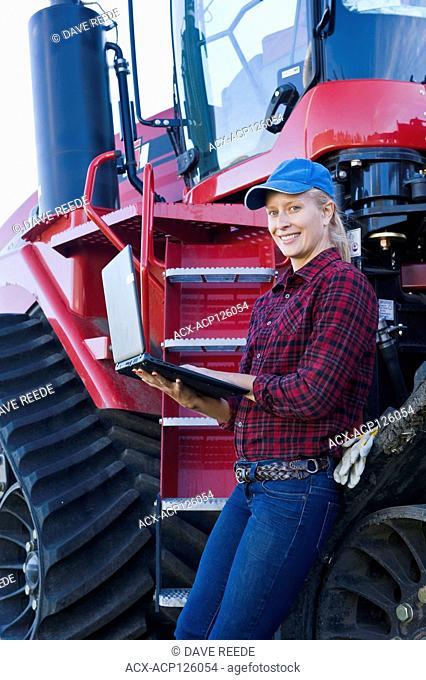girl using a computer next to a Quadtrac tractor, near Dugald, Manitoba