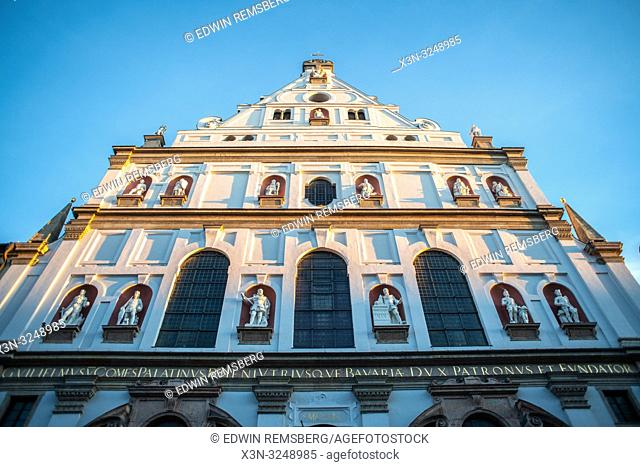 St, Michael's Church detailed in gold and statues is lit by the sun in Munich, Germany