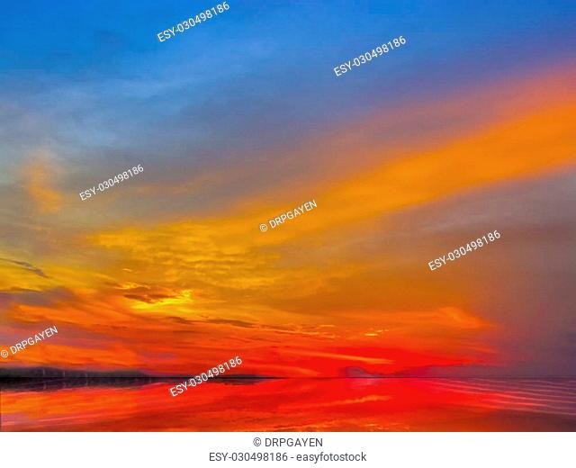 Sunset sky of deep multiple colors of after glow- scaterred rays of lights and its reflection on water