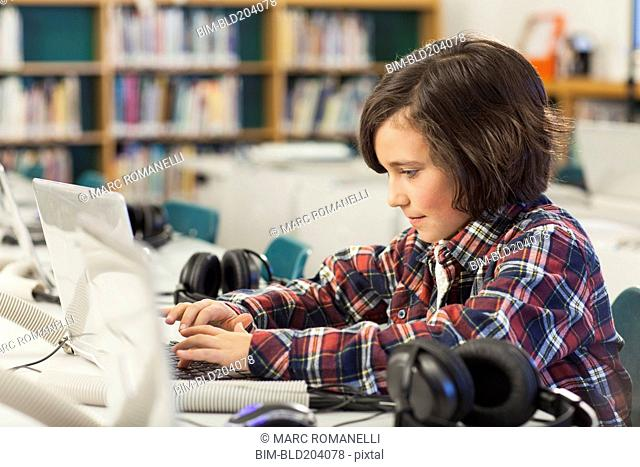 Caucasian boy using laptop in library
