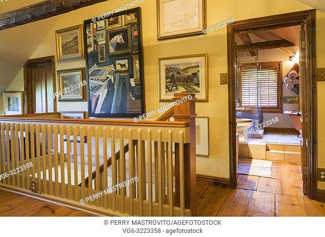 Closed guest bedroom and opened main bathroom doors plus railing surrounding the staircase on the hallway on the upper floor inside an old circa 1850 Canadiana...