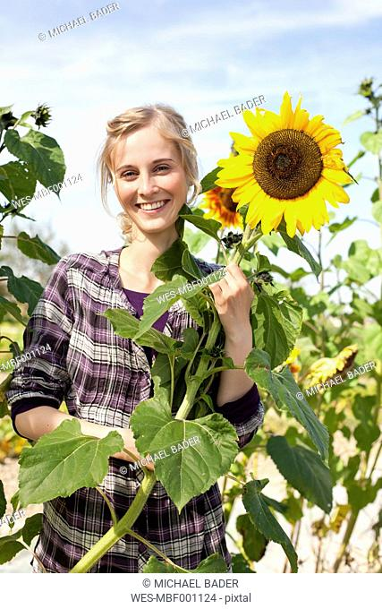 Germany, Saxony, Young woman with sunflower, smiling