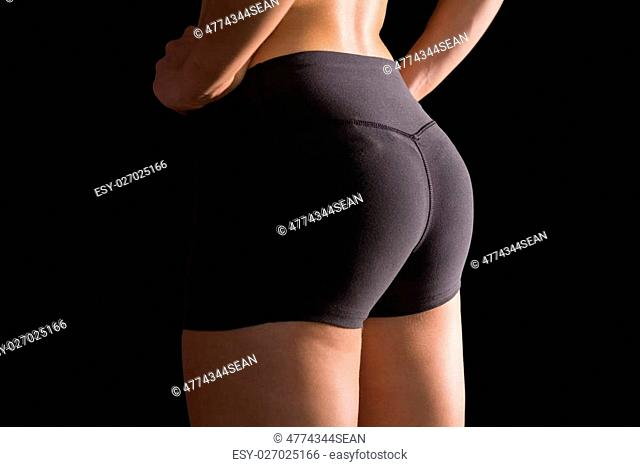Mid section of sporty young woman wearing sportswear posing on black screen