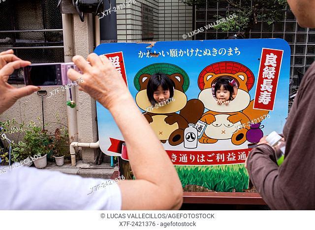 Mother taking pictures in Taito city Street,next to Sensoji Temple,Asakusa, Tokyo, Japan, Asia
