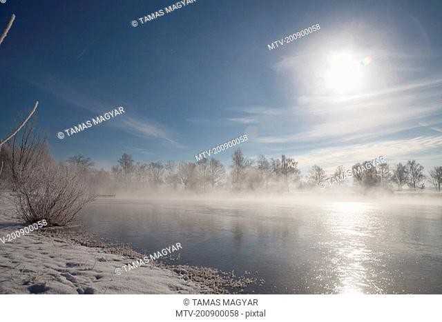 Sun shining over lake in winter, Eichenau, Fürstenfeldbruck, Bavaria, Germany