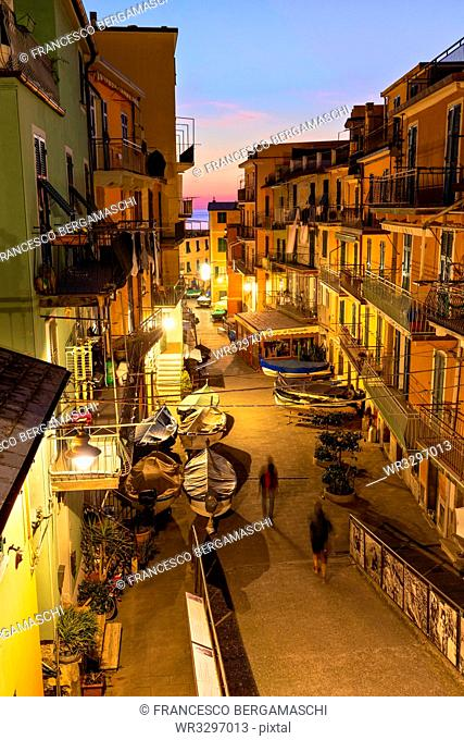 Tourists walks in the main street of Manarola at dusk, Cinque Terre, UNESCO World Heritage Site, Liguria, Italy, Europe