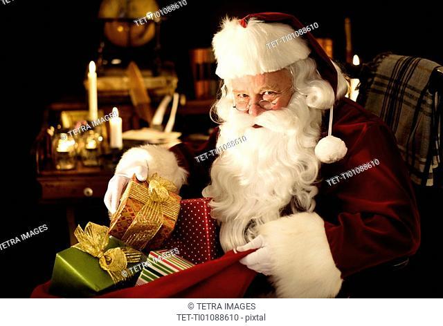 Santa Claus packing Christmas presents to sack