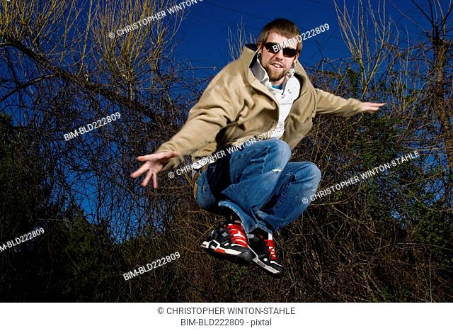 Man wearing sunglasses jumping for joy in forest