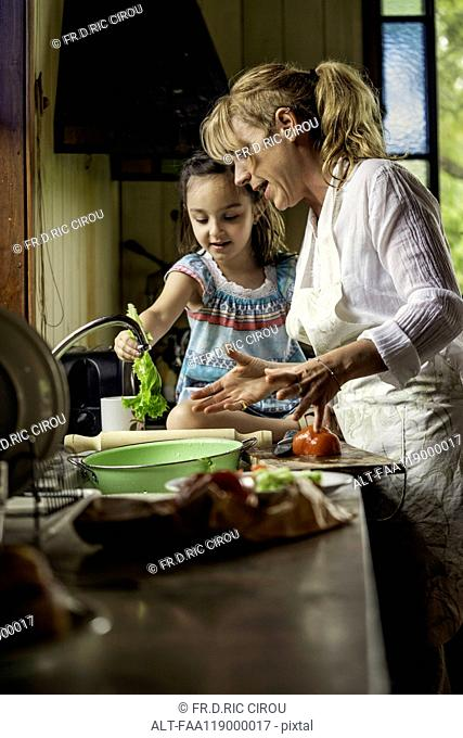 Mature woman teaching her granddaughter in kitchen