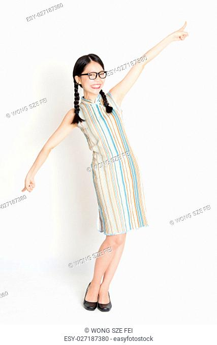 Portrait of young Asian girl in traditional qipao dress finger pointing at something, full length standing on plain background