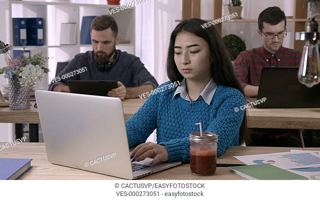 Woman working with documents and laptop in office