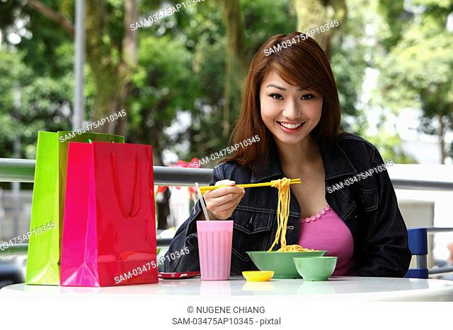 Young woman sitting outside eating noodles
