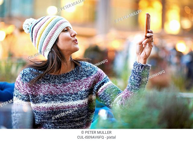 Portrait of mature woman taking smartphone selfie at sidewalk cafe