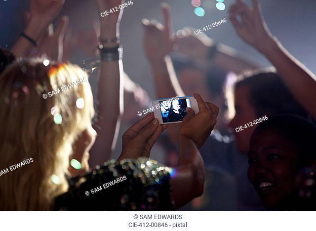 Woman with camera phone photographing friends on dance floor of nightclub
