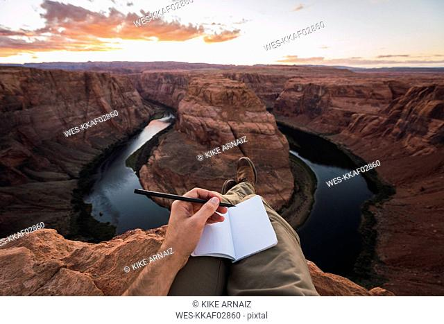USA, Arizona, Colorado River, Horseshoe Bend, young man on viewpoint, notebook