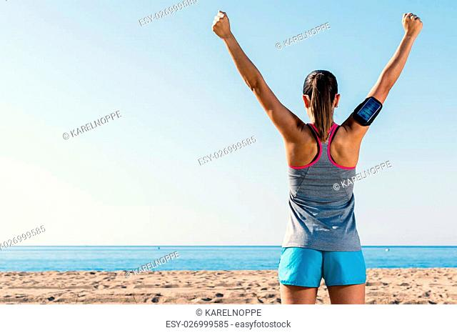 Medium shot rear view of female runner raising arms.Girl standing with winning attitude at sea front