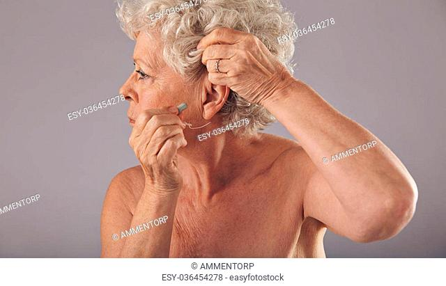 Side view portrait of a senior woman inserting a hearing aid in her ear against grey background. Modern hearing aid for old people