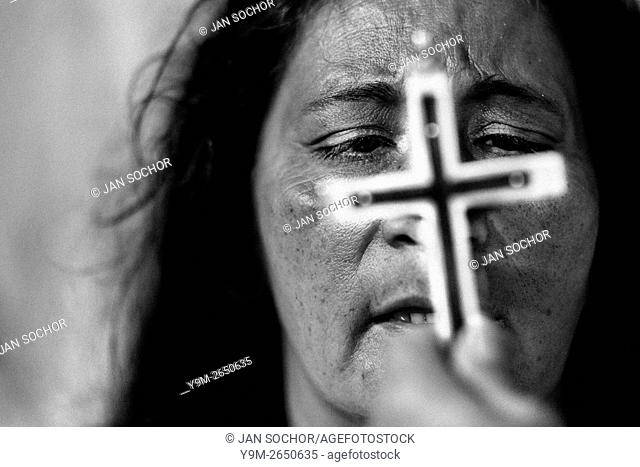 A face of a Colombian woman is seen behind the crucifix during the religious healing ceremony performed at a house church in Bogota, Colombia, 10 March 2016
