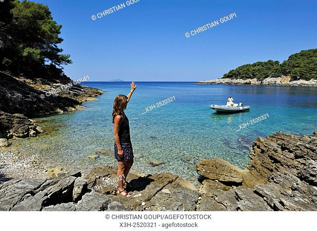 young woman standing on rocks at a creek of Mrcara islet at the north-west of Lastovo island, Croatia, Southeast Europe