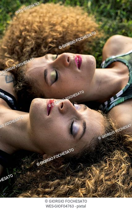 Portrait of rouged twin sisters lying side by side on a meadow