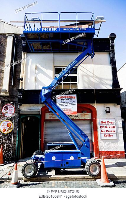 Raised hydraulic cherry picker platform used by decorators beside a building in Temple Bar