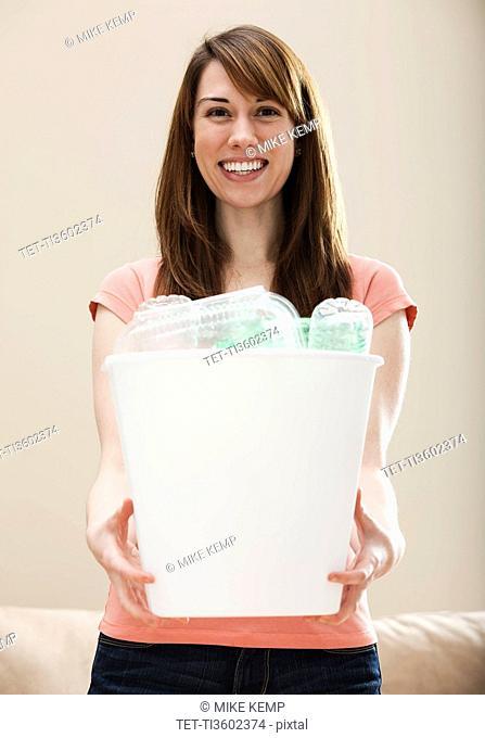 Studio portrait of smiling woman holding recycling bin in plastic bottle
