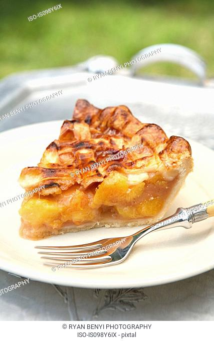 Slice of peach pie on plate