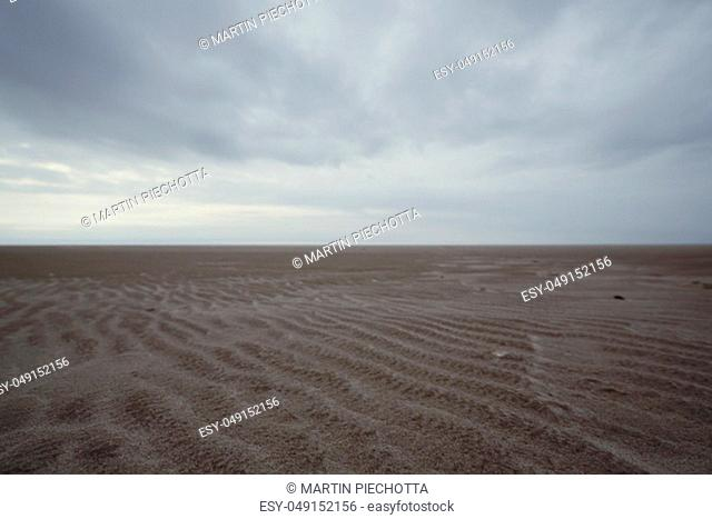 Ground view of sandy beach on cloudy day on seashore. Landscape with straight horizon line dividing picture in two halves horizontally, Amrum, Germany
