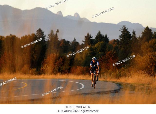 Man road cycling at Iona Beach Regional Park. Richmond, British Columbia, Canada