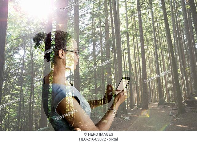 Digital composite businesswoman using cell phone in woods