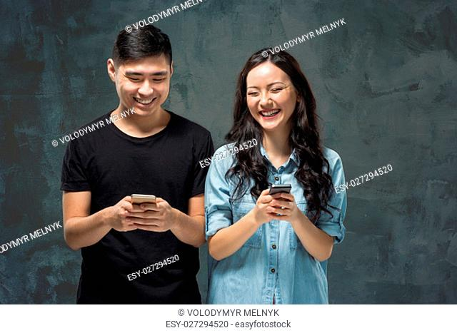 Asian young couple using cellphone, closeup studio portrait on gray