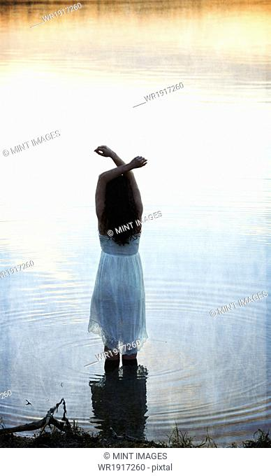 A woman in a white dress in shallow water at dusk