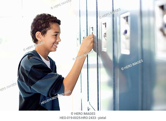 male middle school student opening locker