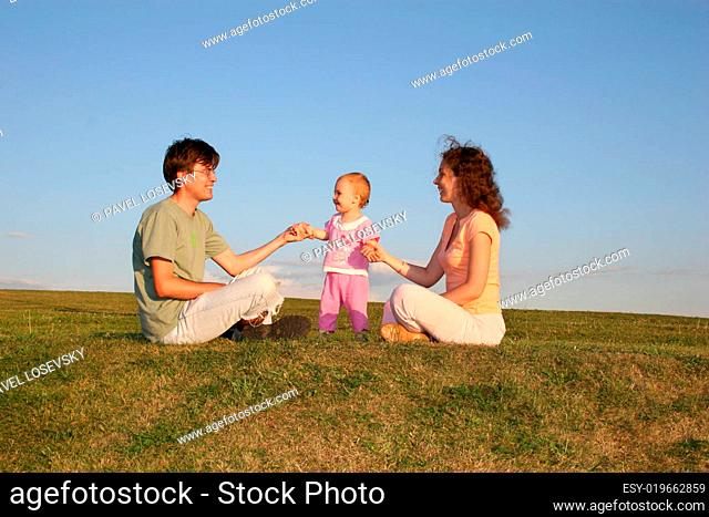 family with baby sit on meadow