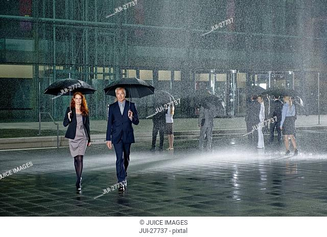 Two businesspeople walking in the rain holding umbrellas